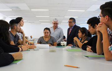 Director general del AGN, Carlos Ruiz Abreú, de pie junto al Subsecretario de Empleo del Gobierno Federal, Horacio Duarte, al extremo de una mesa al rededor de la cual se encuentran sentados 7 becarios del programa jóvenes construyendo el futuro