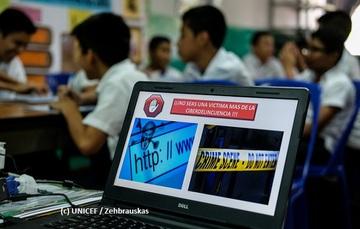 Niños en un salón de clases equipado con computadoras personales.