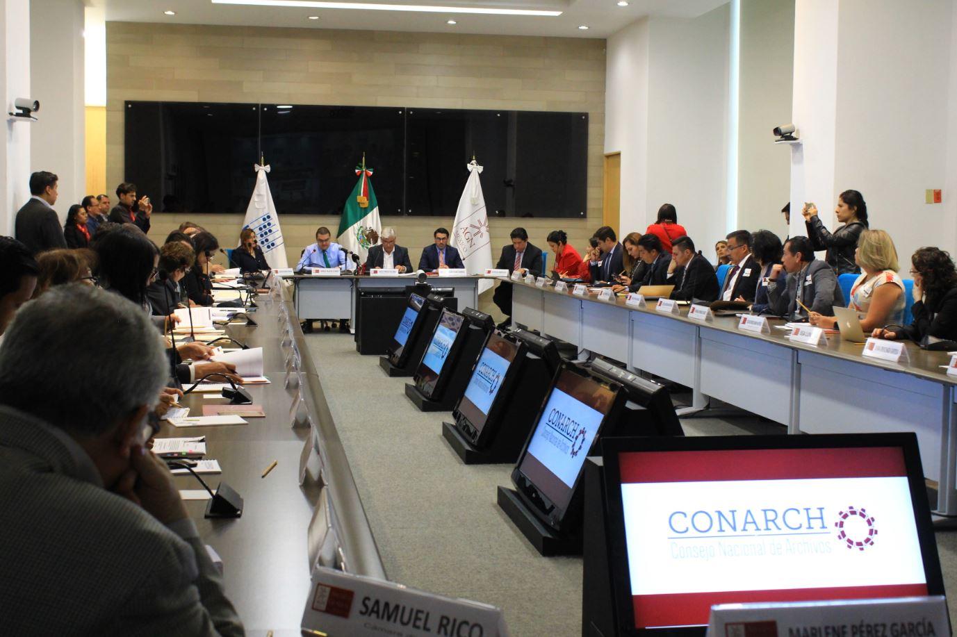 Sala con 42 personas sentadas al rededor de mesas que conforma un gran rectángulo.