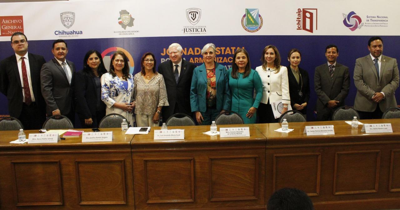 De pie, frente a la cámara y tras la mesa de presidium, aparecen los 12 panelistas de la Jornada Estatal para la armonización legislativa en Chihuahua
