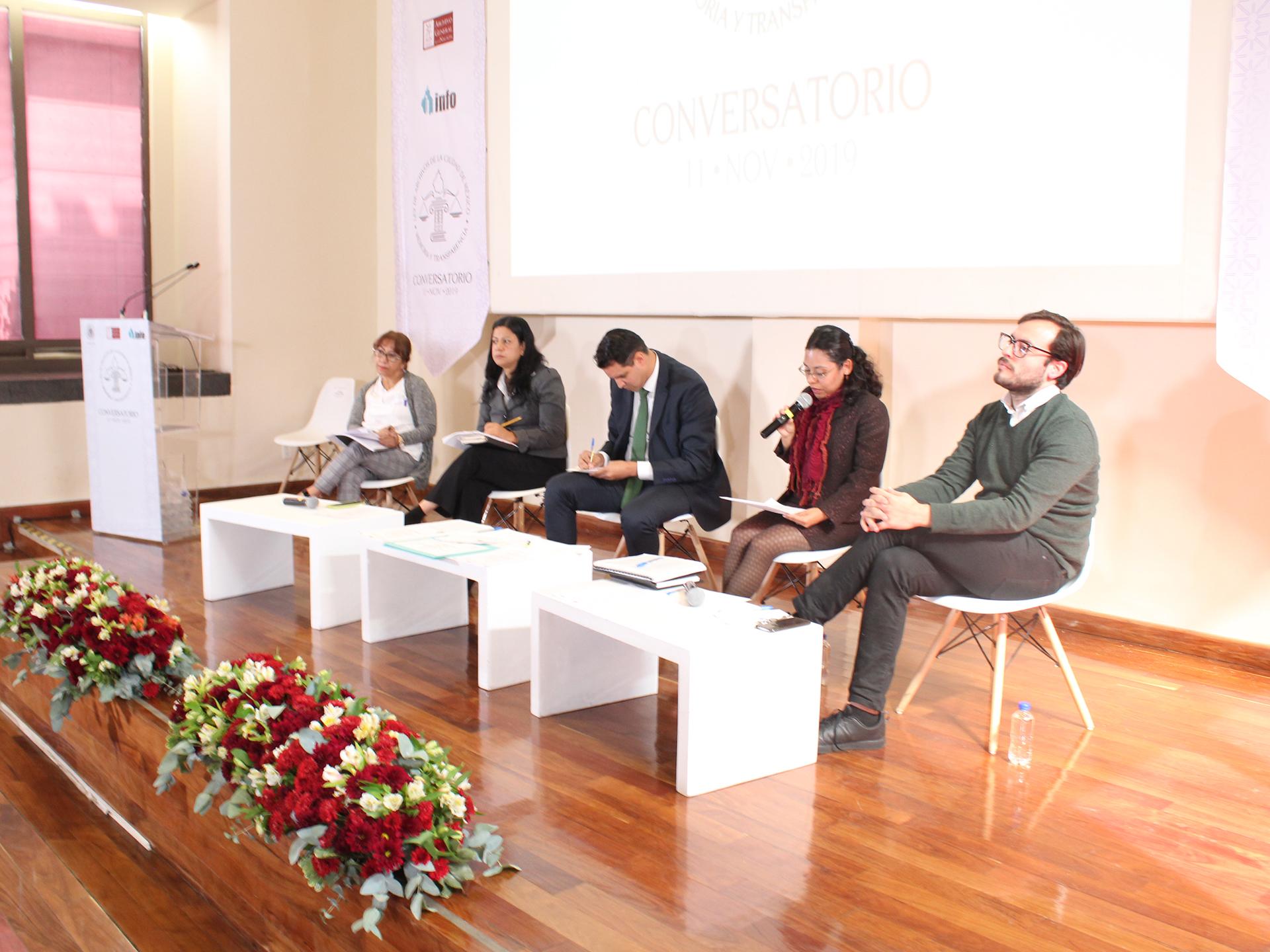Fotografía de 5 panelistas sentados en el podio del auditorio del AGN
