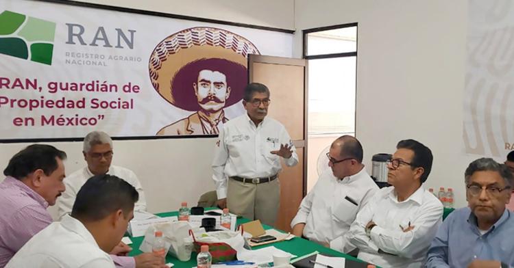 El Director en Jefe del RAN explica a asistentes de mesa agraria. Lo miran atento.