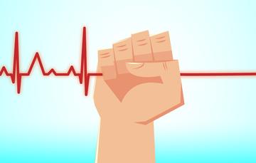 Una mano agarrando la línea que marca el latido del corazón en un electrocardiograma.