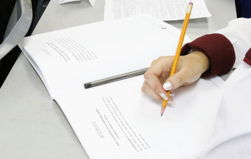 Manos de una joven mujer escribiendo sobre cuaderno