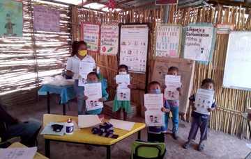 Niños y maestra mostrando sus materiales.