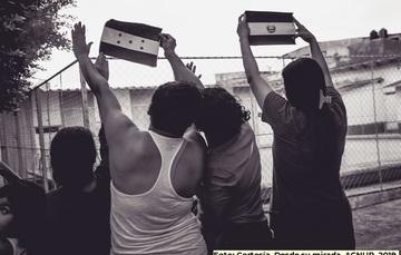 Mujeres migrantes levantando las manos y mostrando las banderas de sus países