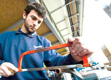 Trabajador cortando un tubo.
