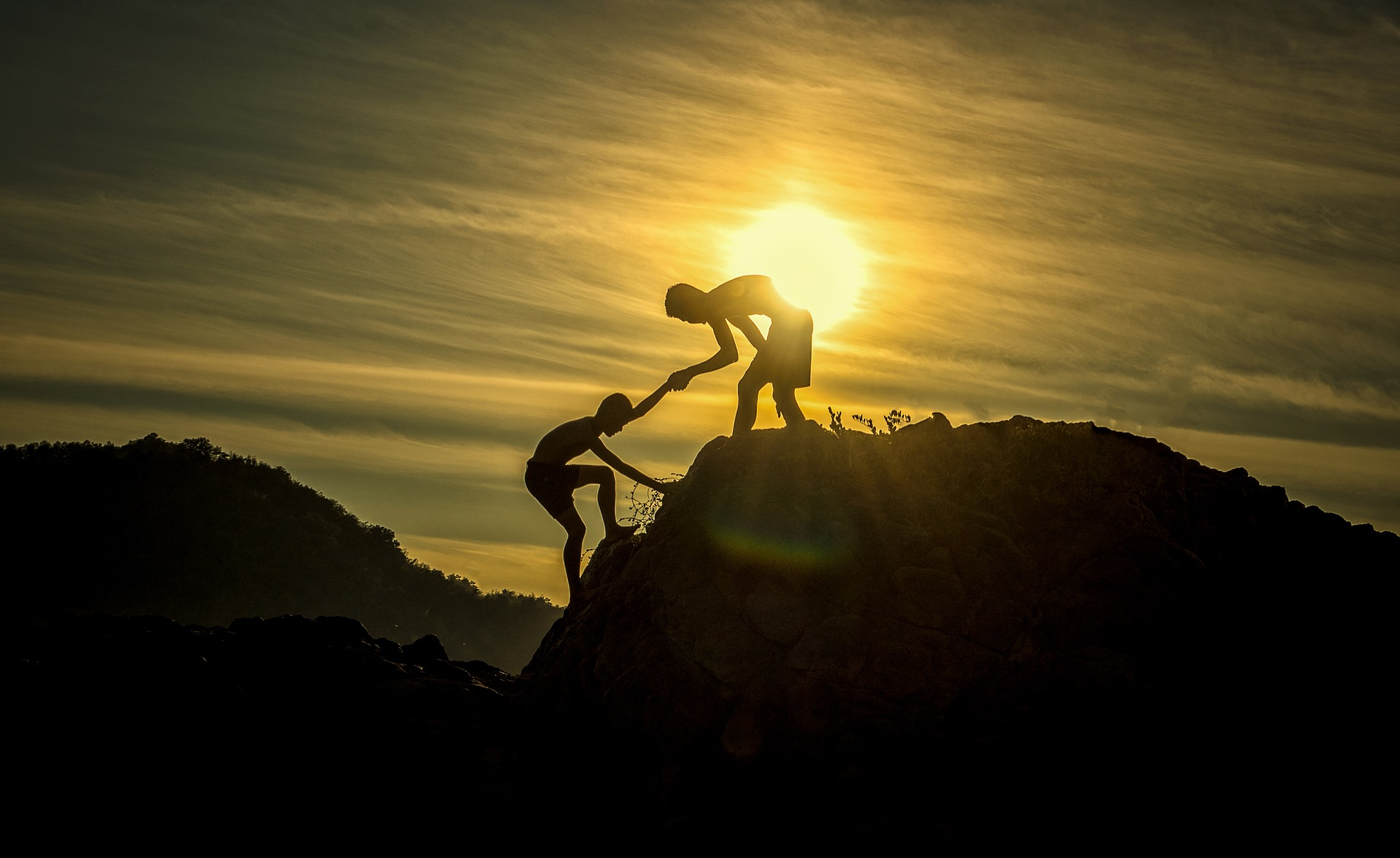 Foto a contraluz de dos montañas y dos personas subiendo.