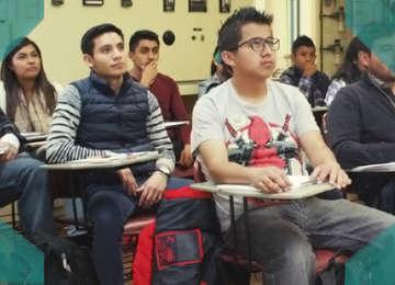 Alumnos sentados en salón de clases