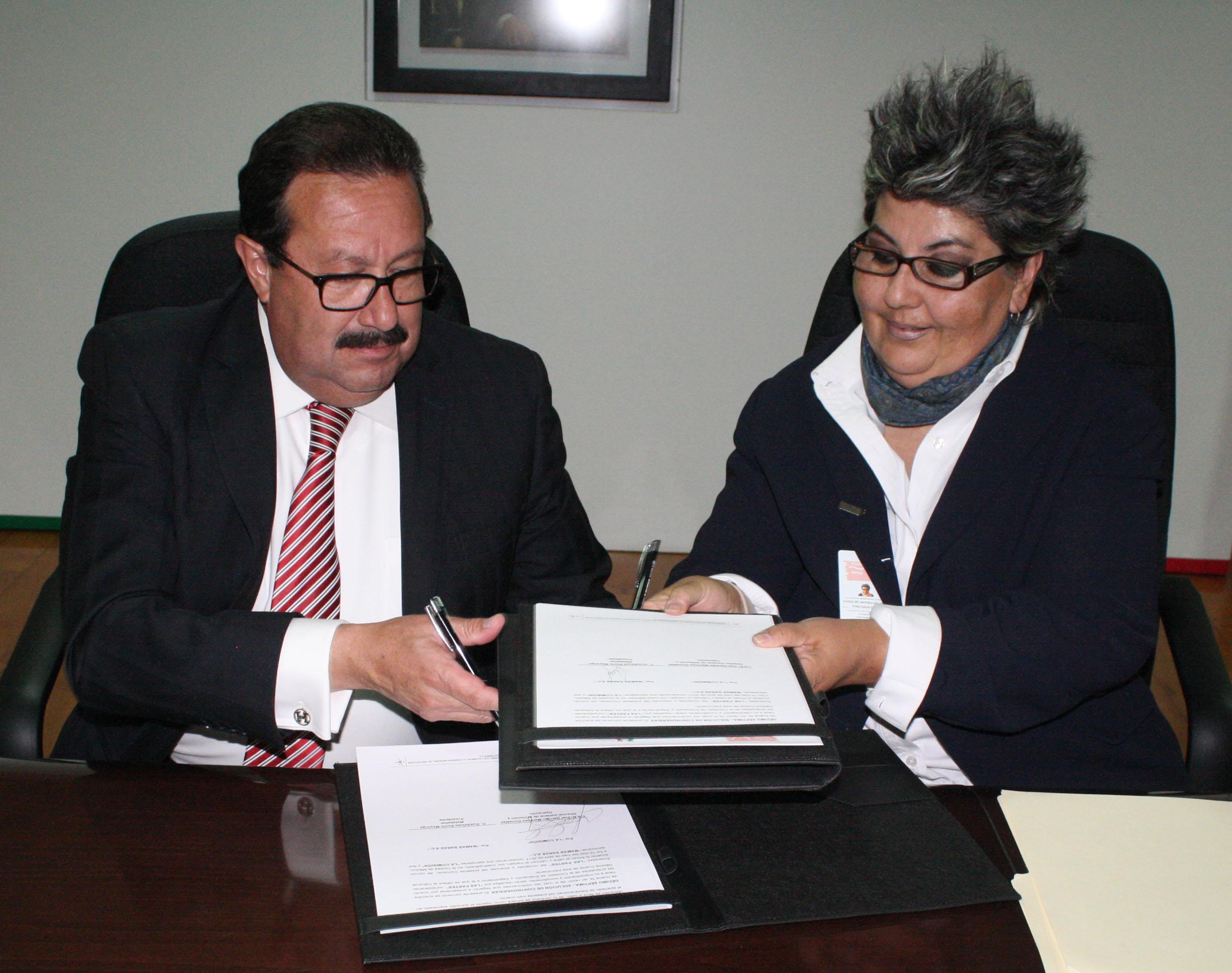 Firmando el convenio.