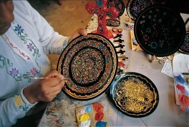 Artesano pintando a mano un plato decorativo