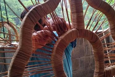 Artesano trabajando en una pieza de fibra vegetal