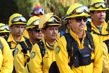 combatientes de incendios forestales recibiendo instrucciones para movilización a Canadá