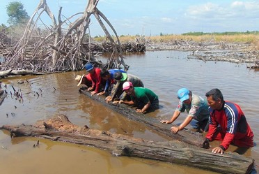Grupo de voluntarios retirando troncos para abrir canal de agua