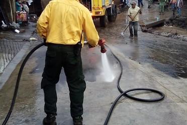 Comabatiente de CONAFOR limpia con manguera calles afetcadas por inundación en Perabán, Michpoacán.