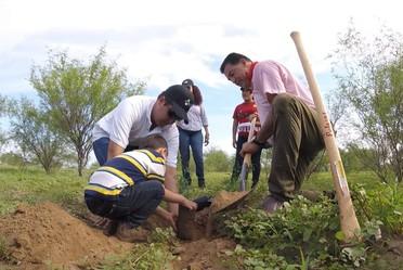 Grupo de personas y niño plantando un árbol.