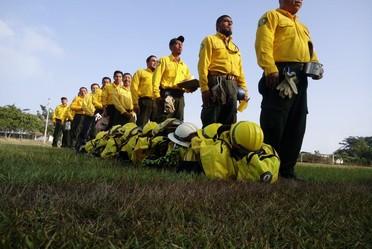 Combatientes en capacitación formados en fila con su equipo personal a un costado.