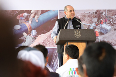 Imagen del Director General de Conagua, Roberto Ramírez de la Parra frente al estrado. De fondo imágenes del Acuaférico Tramo III Fase E de Querétaro.