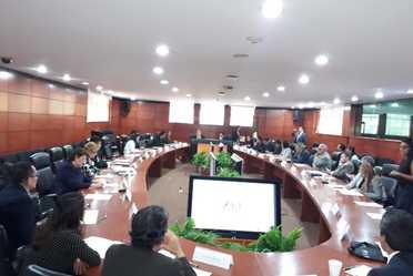Varias personas alrededor de una mesa en reunión.