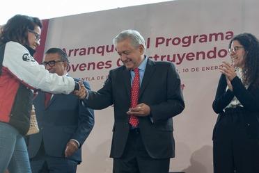 El presidente Andrés Manuel López Obrador entrega tarjeta simbólica a una joven becaria del programa