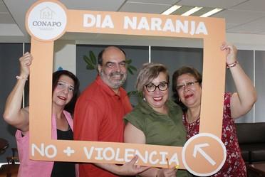 4 personas que laboran en CONAPO, 3 mujeres un hombre sosteniendo un marco naranja.