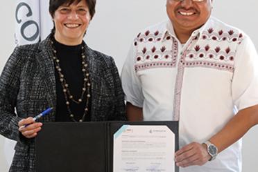 Fotografía en la que aparece de pie la Directora General de Conagua, Blanca Jiménez junto al Títular del Instituto Nacional de los Pueblos Indígenas, Adelfo Regino Montes sosteniendo el Convenio firmado.