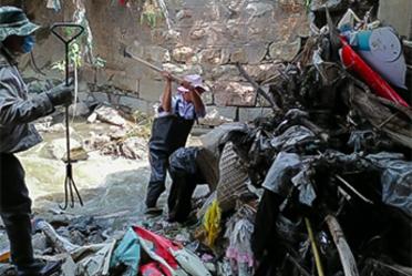 Imagen en la que aparecen dos señores limpiando un cerro de basura.