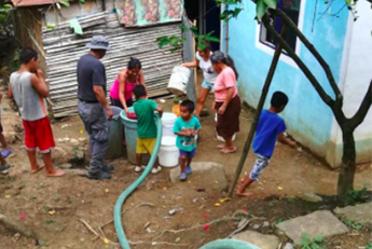 Imagen en la que aparecen varias personas, llenando a través de una manguera sus botes con agua potable.