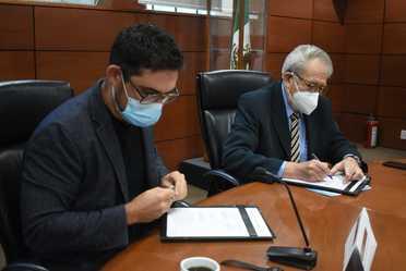 Funcionarios firmando el convenio.