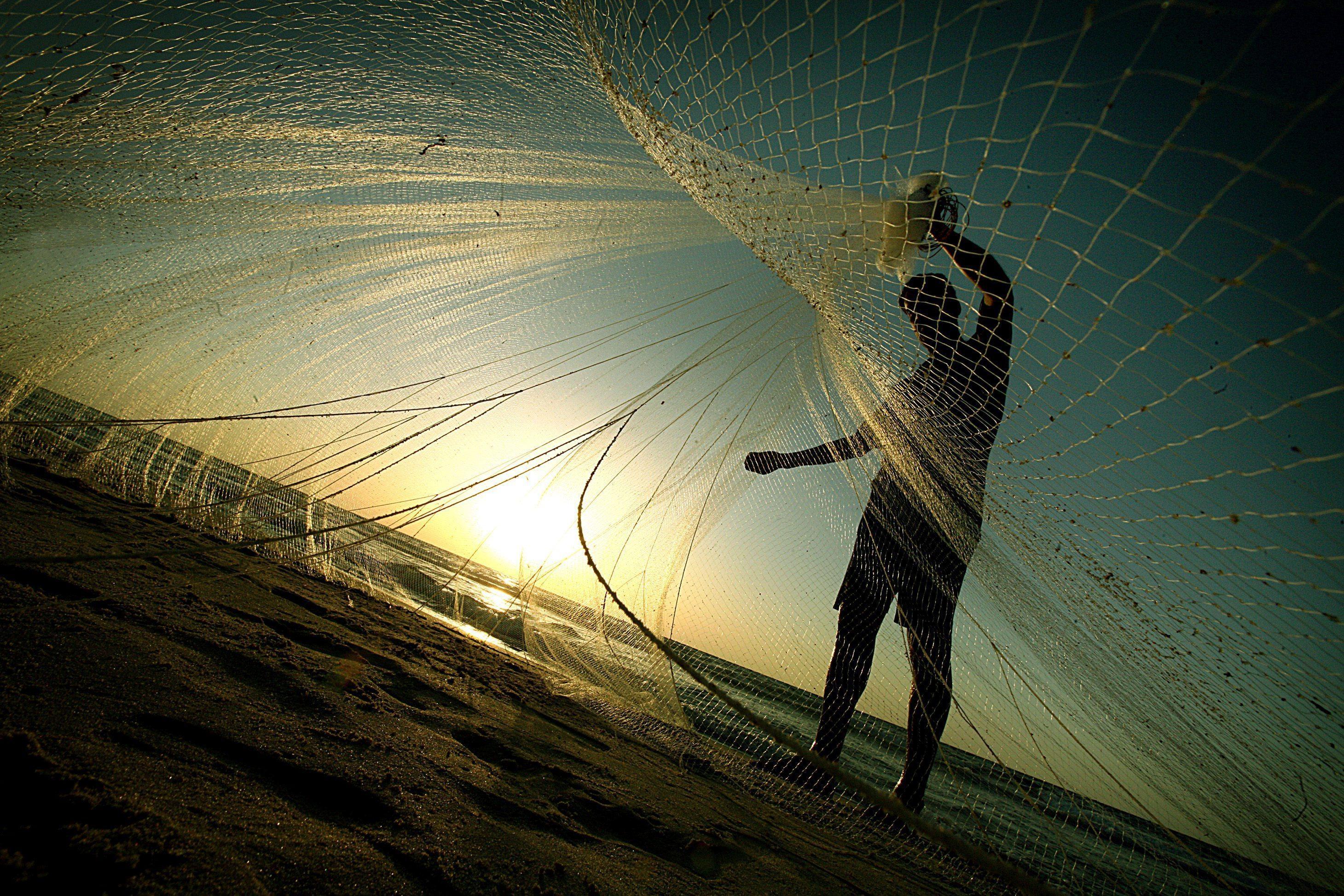 Pescador en la playa con una red