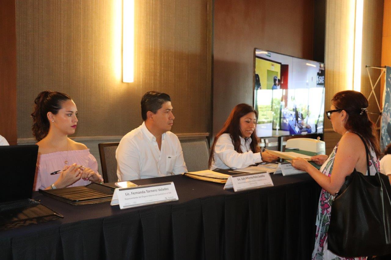 Empleados de la institución organizadora de la licitación pública de inmuebles ante la mesa de registro de participantes, en espera de los interesados.
