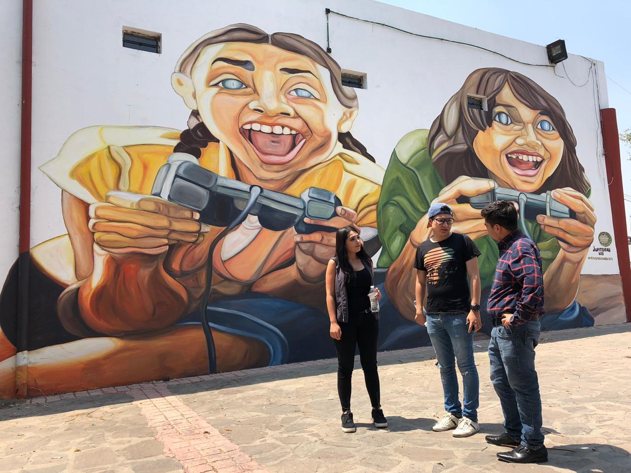 Fotografía a Guillermo Santiago director de IMJUVE donde se encuentra platicando con 2 jóvenes, y detrás puede apreciar un grandioso muro pintado por jóvenes destacando su arte urbano donde se muestran dos adolescentes jugando videojuegos.