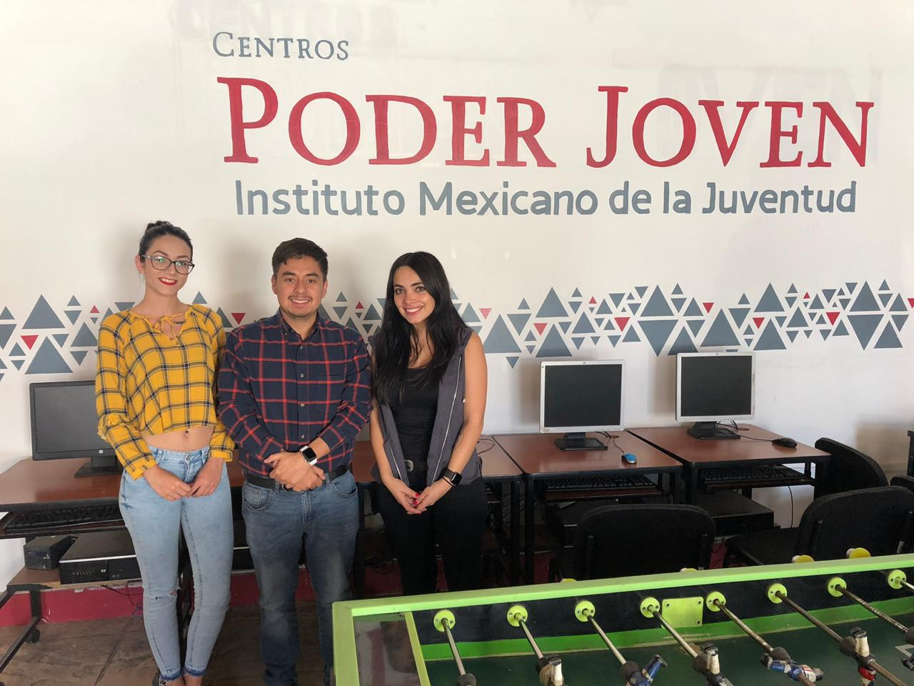 Fotografía al director de Instituto Mexicano de la Juventud Guillermo Santiago junto a dos jóvenes mujeres dentro de un aula de un centro Territorio joven en el estado de Jalisco.