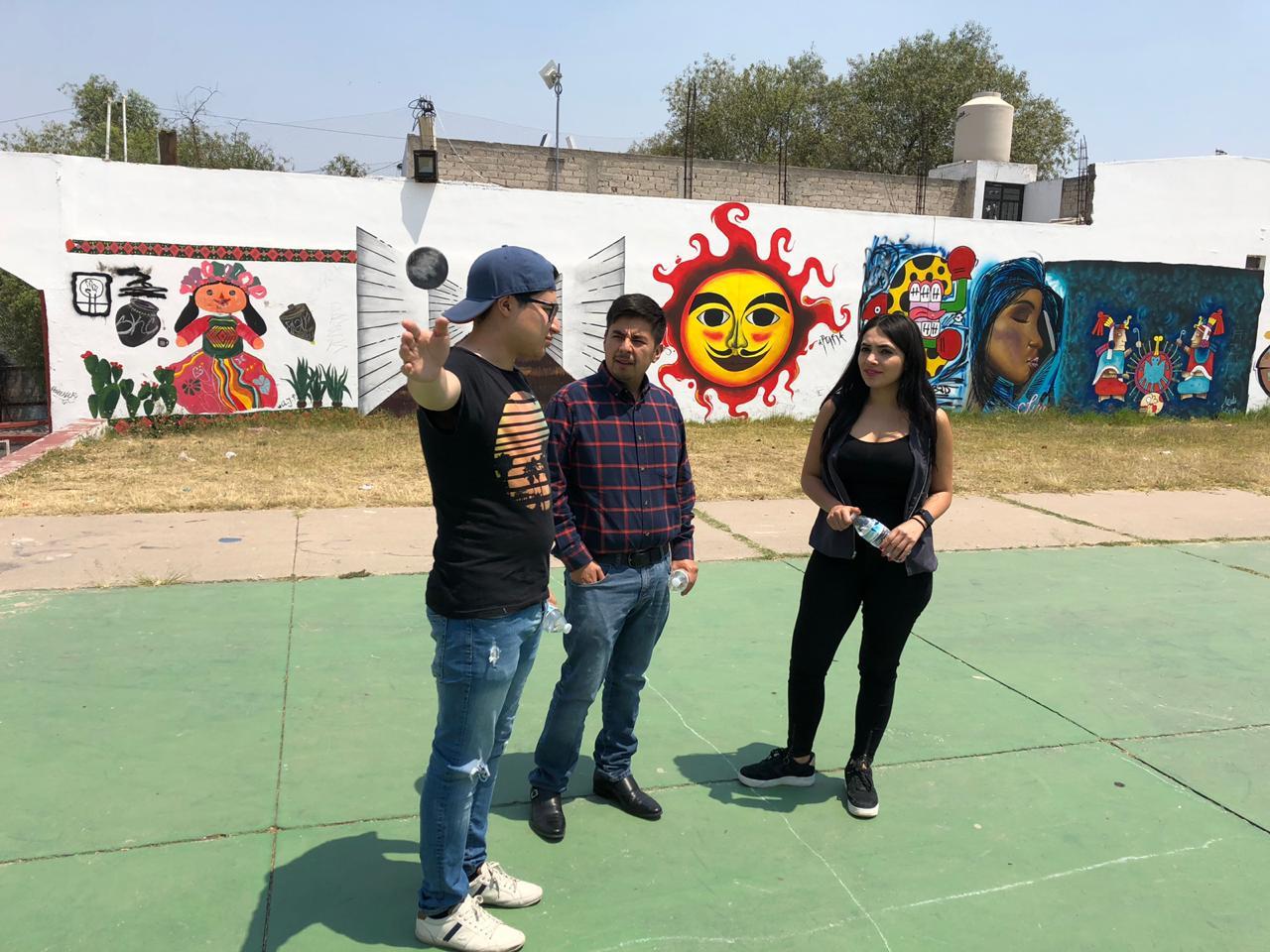 Se le esta dando un recorrido al director del Instituto Mexicano de la Juventud Guillermo Santiago por las instalaciones de un centro de territorio joven y explicando los diferentes significados que tienes los muros de arte urbano, pintados por jóvenes mexicanos.