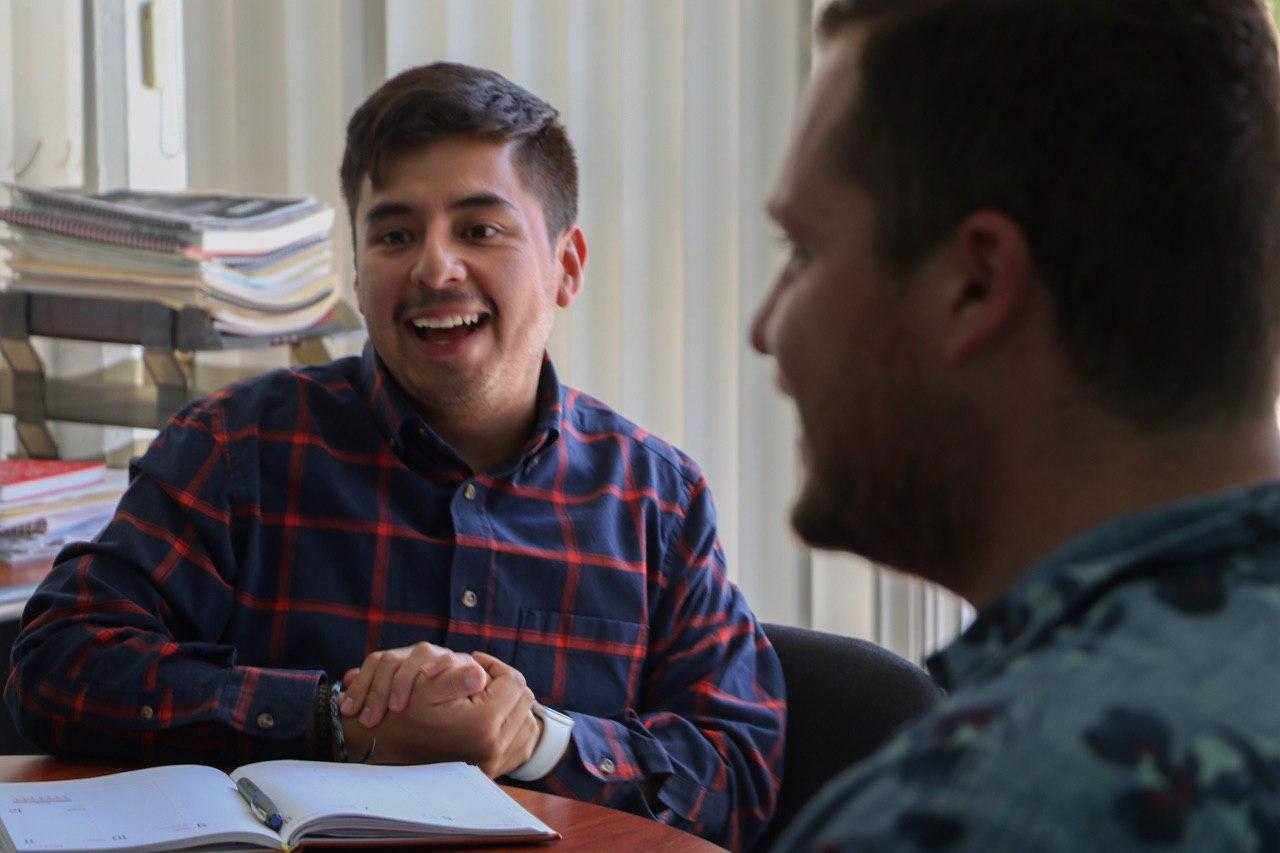 El director del Imjuve, Guillermo Santiago, sonriendo en conversación con dos jóvenes de la Secretaría de Igualdad Sustantiva entre Mujeres y Hombres de Jalisco.