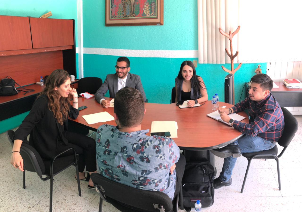 El director Guillermo Santiago está dialogando en una mesa de trabajo con 4 representantes de la Secretaría de Igualdad Sustantiva entre mujeres y hombres de Jalisco intercambiando puntos de vista que tiene como prioridad a mujeres, jóvenes, personas con discapacidad, migrantes e indígenas