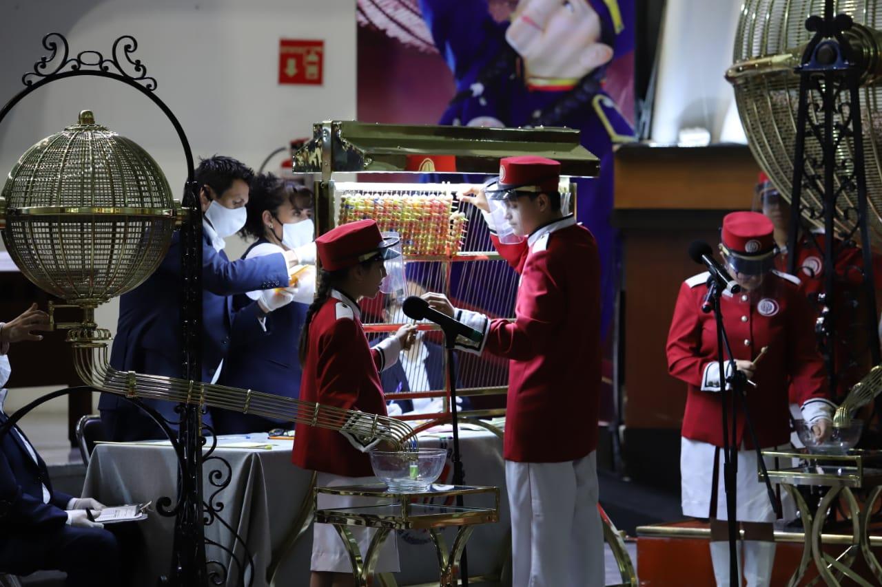 Fotografía de los niños gritones frente al ábaco del sorteo, cantando los premios ganadores
