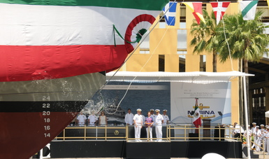 Parte delantera de un barco con botella rota al fondo se observa personas  con la bandera mexicana