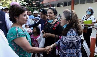 Rosario Robles estrechando la mano a genete beneficiada