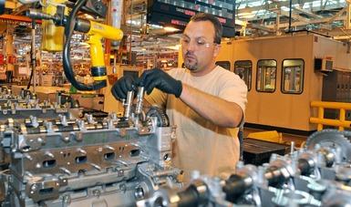 Trabajador armando un motor en una línea de ensamblaje