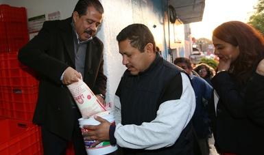 Srio. Eviel Pérez Magaña repartiendo leche a beneficiarios