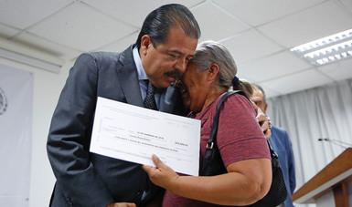 Srio. Eviel Pérez Magaña entregando un cheque a beneficiaria del SVJF