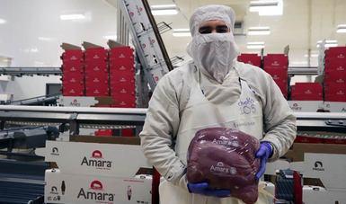 Trabajador de una empacadora de carne sosteniendo un paquete de carne
