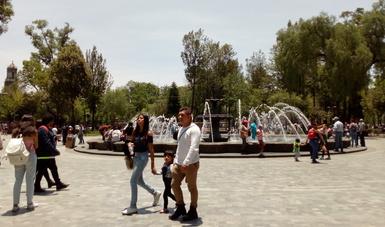 Padre de familia caminando sobre plaza pública en compañía de su esposa e hija