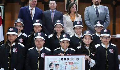 Fotografía Grupal de las personas que participaron en la celebración del Sorteo Mayor alusivo al 29 aniversario del Programa Paisano. En la fotografía aparecen 10 niños gritones acompañados de 4 funcionarios del gobierno.