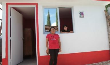 Jefa de familia afuera de casa con cuarto rosa.