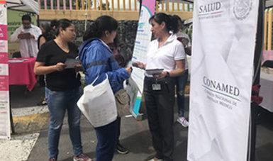 Maestra Sandra Martínez, Subdirectora de Enseñanza de la CONAMED, brindando información y folletos a dos mujeres