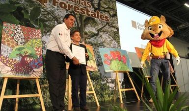 Niño recibe reconocimiento de manos del director de CONAFOR.