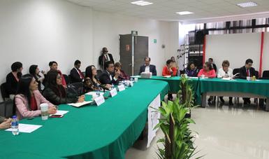 Hombres y mujeres sentados en una reunión.