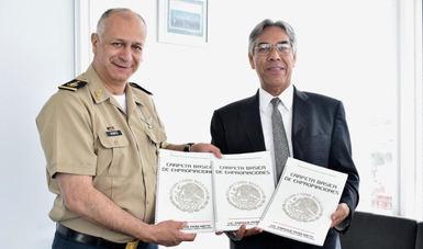 El subsecretario de la SEDATU Enrique González Tiburcio y el al General de Brigada y Justicia Militar, de la Secretaría de la Defensa Nacional Alejandro Ramos Flores, muestran las carpetas de expropiación.